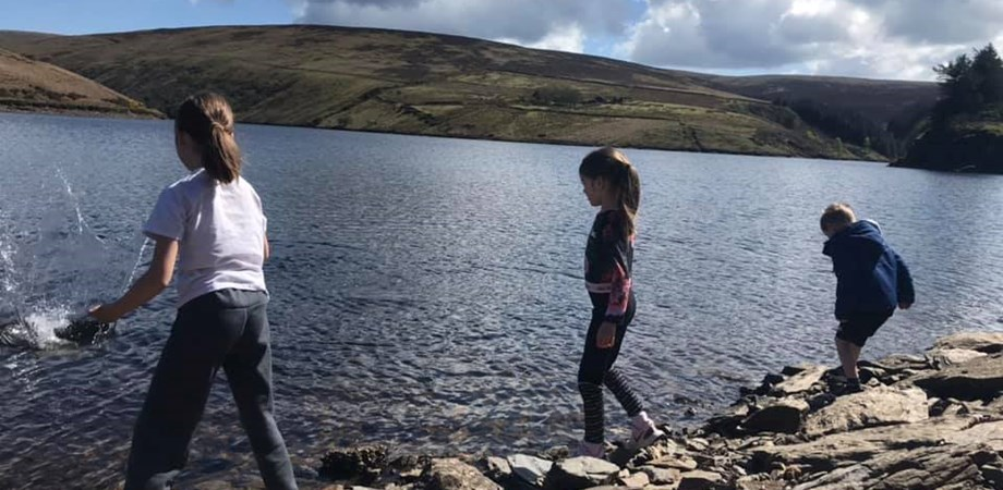 A picture of author of the article, Kathryn's children throwing stones into a reservoir