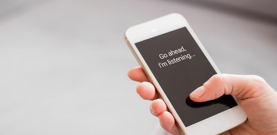 "A phone in somebodies hand displaying the message ""Go ahead, I'm listening..."""